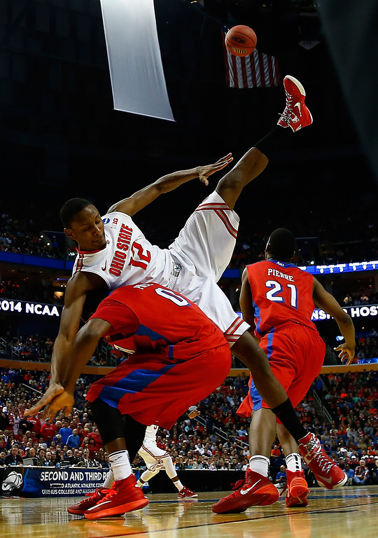 . Sam Thompson #12 of the Ohio State Buckeyes gets tangled with Khari Price #0 of the Dayton Flyers under the basket during the second round of the 2014 NCAA Men\'s Basketball Tournament at the First Niagara Center on March 20, 2014 in Buffalo, New York.  (Photo by Jared Wickerham/Getty Images)