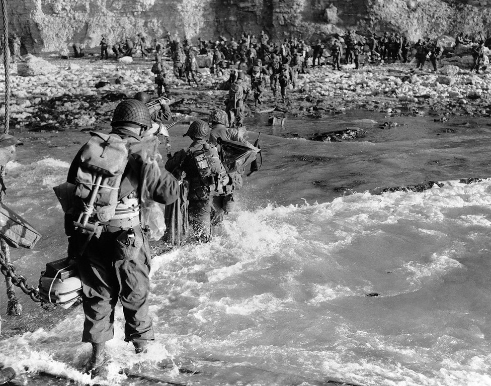 . U.S. reinforcements wade through the surf as they land at Normandy in the days following the Allies\' June 1944, D-Day invasion of occupied France. (AP Photo)