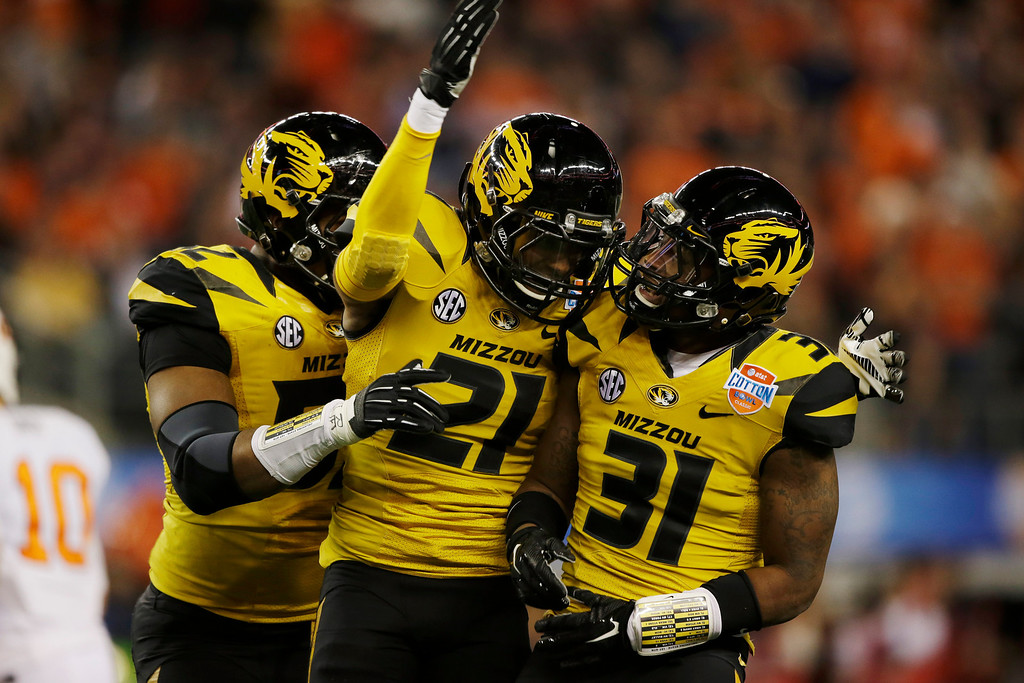 . Missouri defensive back E.J. Gaines (31) celebrates his interception against Oklahoma State with safety Ian Simon (21) and defensive lineman Michael Sam (52) during the first half of the Cotton Bowl NCAA college football game on Friday, Jan. 3, 2014, in Arlington, Texas. (AP Photo/Tim Sharp)