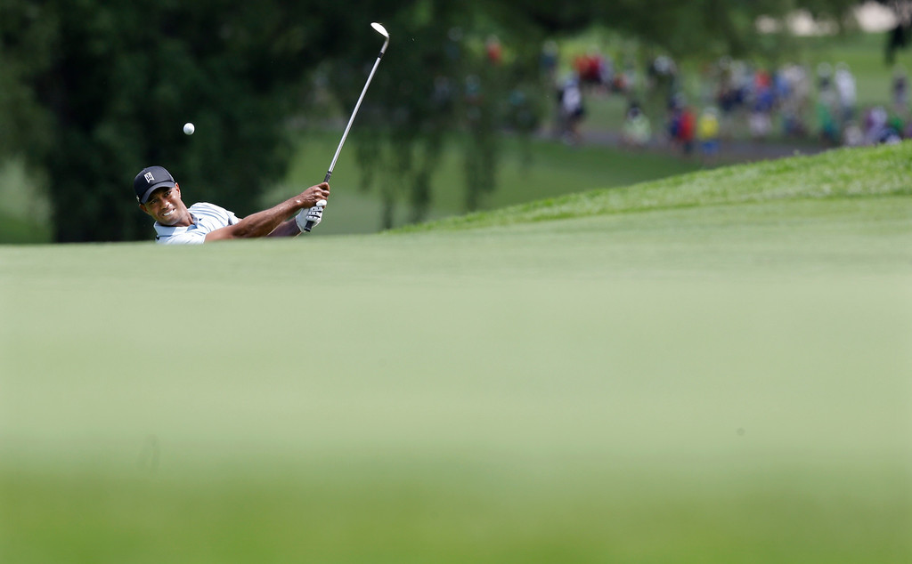 . Tiger Woods hits to the ninth green during the first round of the PGA Championship golf tournament at Oak Hill Country Club, Thursday, Aug. 8, 2013, in Pittsford, N.Y. (AP Photo/Patrick Semansky)