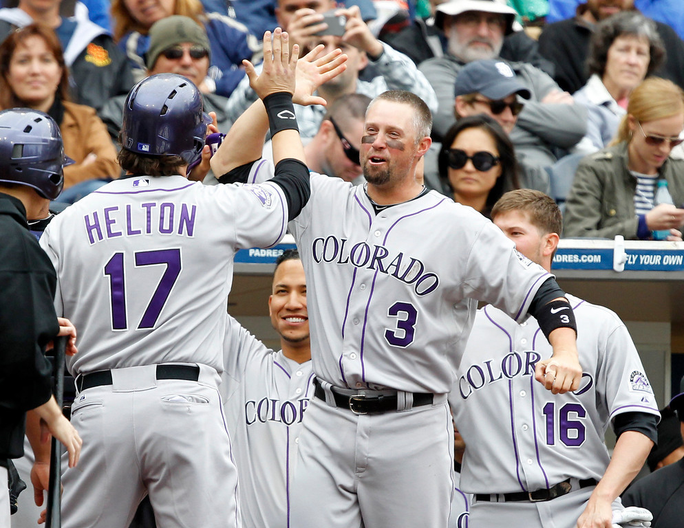 . Colorado Rockies\' Michael Cuddyer (3) congratulates Rockies\' Todd Helton, left, for hitting a pinch-hit, two-run home run against the San Diego Padres in the seventh inning during a baseball game Sunday, April 14, 2013, in San Diego. (AP Photo/Alex Gallardo)
