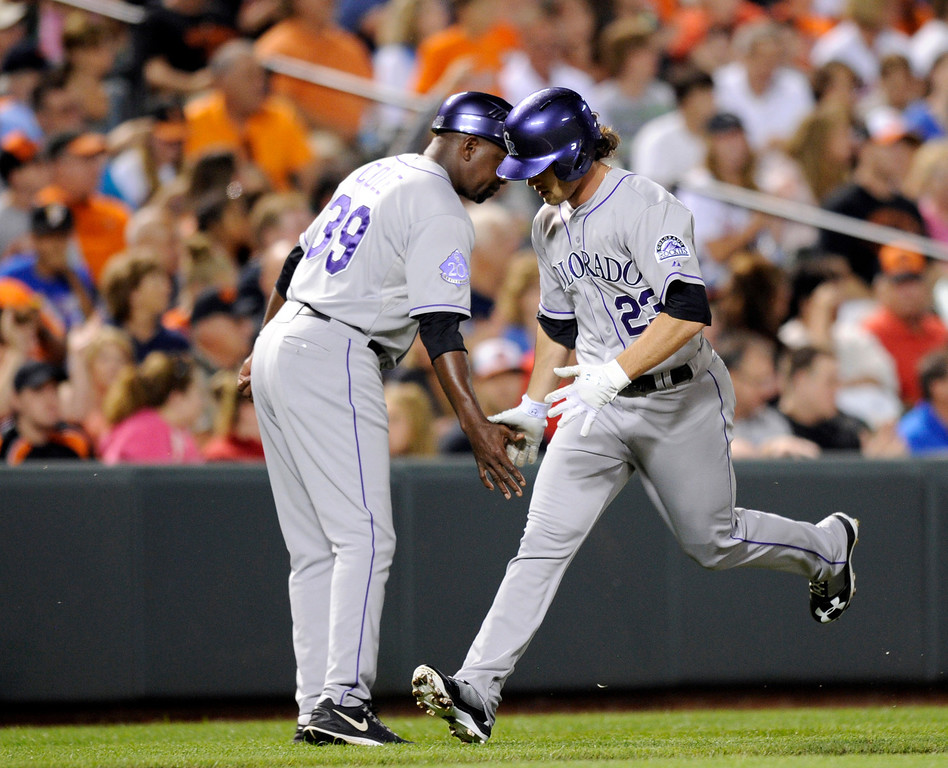 . Colorado Rockies\' Charlie Culberson (23) is greeted by third base coach Stu Cole (39) after he hit a home run against the Baltimore Orioles during the sixth inning of a baseball game, Friday, Aug. 16, 2013, in Baltimore. (AP Photo/Nick Wass)