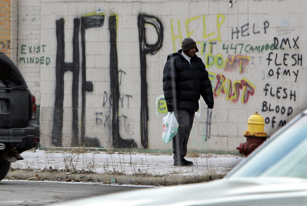 . In a Dec. 12, 2008 file photo, a pedestrian walks by graffiti in downtown Detroit. On Thursday, July 18, 2013 Detroit became the largest city in U.S. history to file for bankruptcy when State-appointed emergency manager Kevyn Orr asked a federal judge for municipal bankruptcy protection. (AP Photo/Carlos Osorio, FILE)