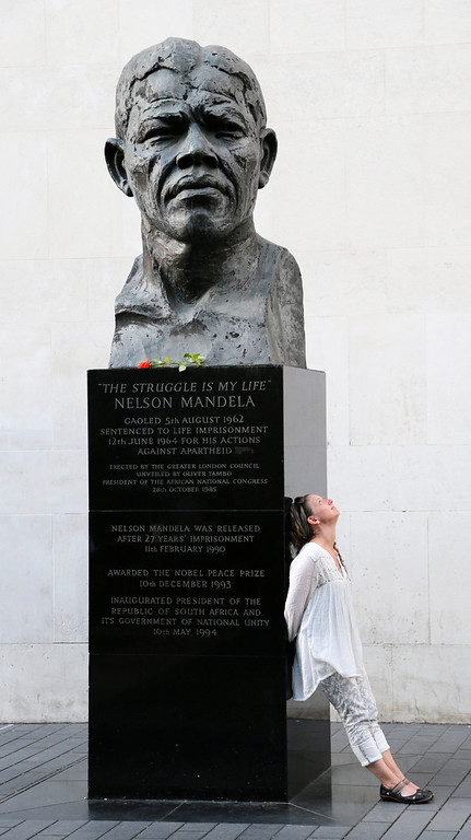 . A woman leans against a bust of former South African President Nelson Mandela, outside Royal Festival Hall in London June 25, 2013. Mandela remained in a critical condition in hospital on Tuesday after being admitted more than two weeks ago with a lung infection, the government said. The statue was erected in 1985, before his release after 27 years captivity in 1990, his award of the Nobel Peace Prize in 1993 and his election as president of the Republic of South Africa in 1994. REUTERS/Chris Helgren