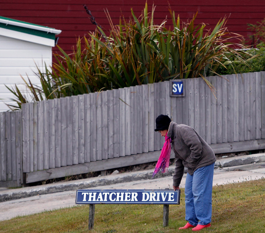 . A woman touches the (Margaret) Thatcher Drive sign in Stanley March 10, 2013. Residents of the Falkland Islands started voting on Sunday in a sovereignty referendum that seeks to counter Argentina\'s increasingly assertive claim over the British-ruled territory. REUTERS/Marcos Brindicci