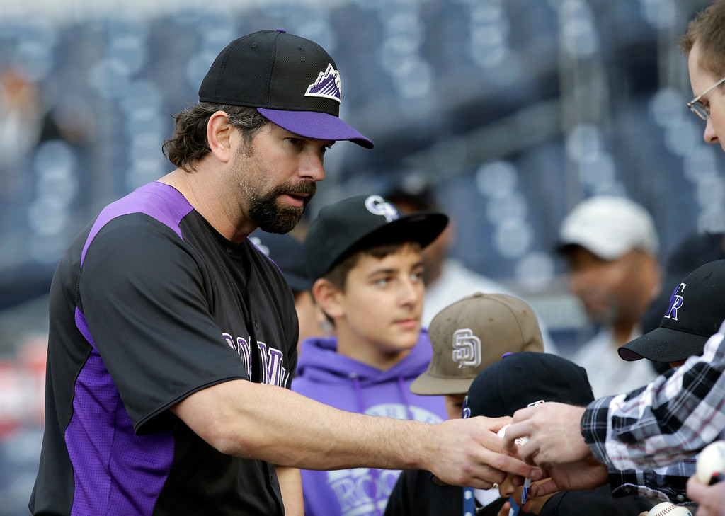 . Colorado Rockies\' Todd Helton signs autographs after batting practice for a baseball game against the San Diego Padres, Friday April 12, 2013, in San Diego. (AP photo/Lenny Ignelzi)