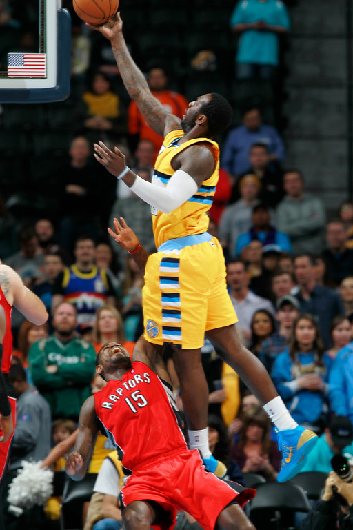 . Denver Nuggets forward J.J. Hickson, top, is called for charging as he drives to shoot over Toronto Raptors forward Amir Johnson in the first quarter of an NBA basketball game in Denver, Friday, Jan. 31, 2014. (AP Photo/David Zalubowski)