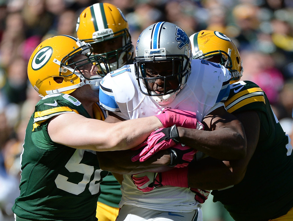 . Reggie Bush #21 of the Detroit Lions is wrapped up by A.J. Hawk #50 of the Green Bay Packers during the second quarter at Lambeau Field on October 6, 2013 in Green Bay, Wisconsin.  (Photo by Harry How/Getty Images)