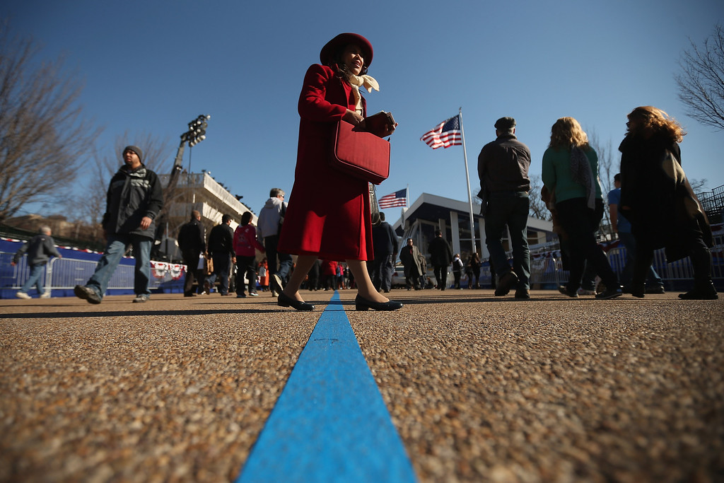 . Christian evangelist Mary Clement of Silver Spring, Maryland, sings and reads from her Bible as she walks along Pennsylvania Avenue outside the White House as U.S. President Barack Obama takes the Oath of Office inside January 20, 2013 in Washington, DC. One day before the public inaugural ceremony at the U.S. Captiol, Obama was officially sworn in for his second term during a private ceremony surrounded by friends and family in the Blue Room of the White House.  (Photo by Chip Somodevilla/Getty Images)