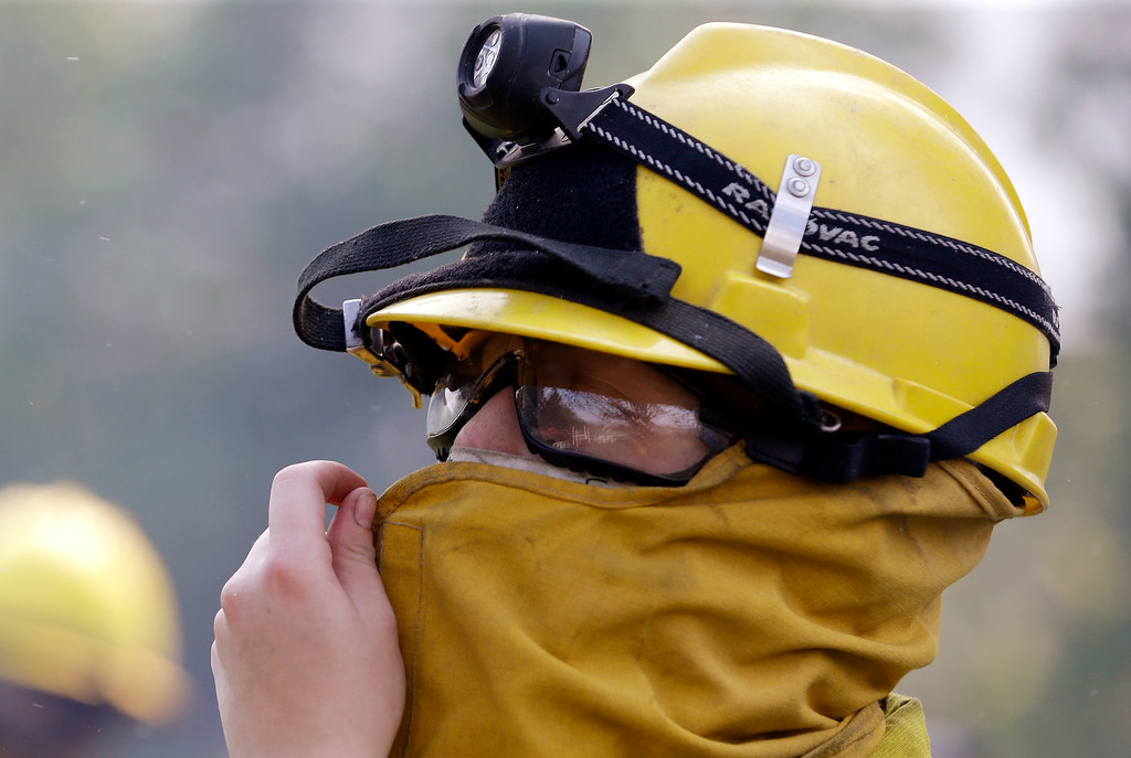 . Firefighter Kate Hunter, of the San Juan, Wash., Fire District, adjusts her protective gear before heading into the field Friday, July 18, 2014, in Winthrop, Wash. A fire racing through rural north-central Washington destroyed about 100 homes, leaving behind smoldering rubble, solitary brick chimneys and burned-out automobiles as it blackened hundreds of square miles on Friday. (AP Photo/Elaine Thompson)