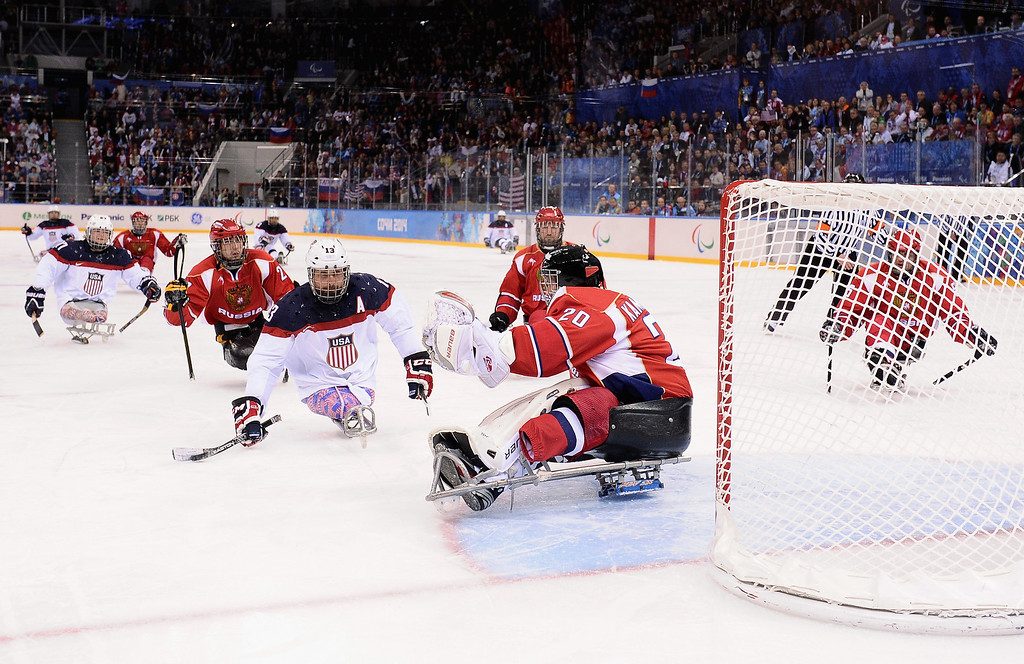 . Joshua Sweeney of the United States scores past Vladimir Kamantcev of Russia during the Ice Sledge Hockey Gold Medal game between the United States and Russia on day eight of the Sochi 2014 Paralympic Winter Games at Shayba Arena on March 15, 2014 in Sochi, Russia.  (Photo by Dennis Grombkowski/Getty Images)