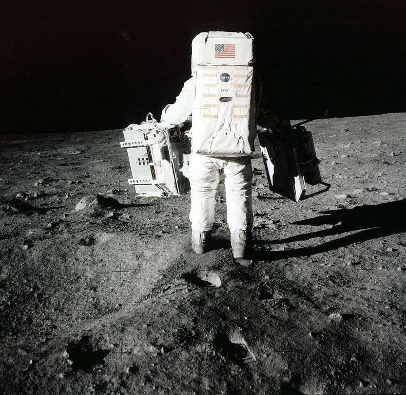 . Edwin  Buzz  Aldrin carries scientific experiments to a deployment site south of the lunar module Eagle. One experiment involved the inner composition of the moon, and another tried to determine the exact distance from Earth. Photo was taken by Neil Armstrong of the Apollo 11 mission in July 1969. From the book  Full Moon  (Knopf) by Michael Light. (AP Photo)