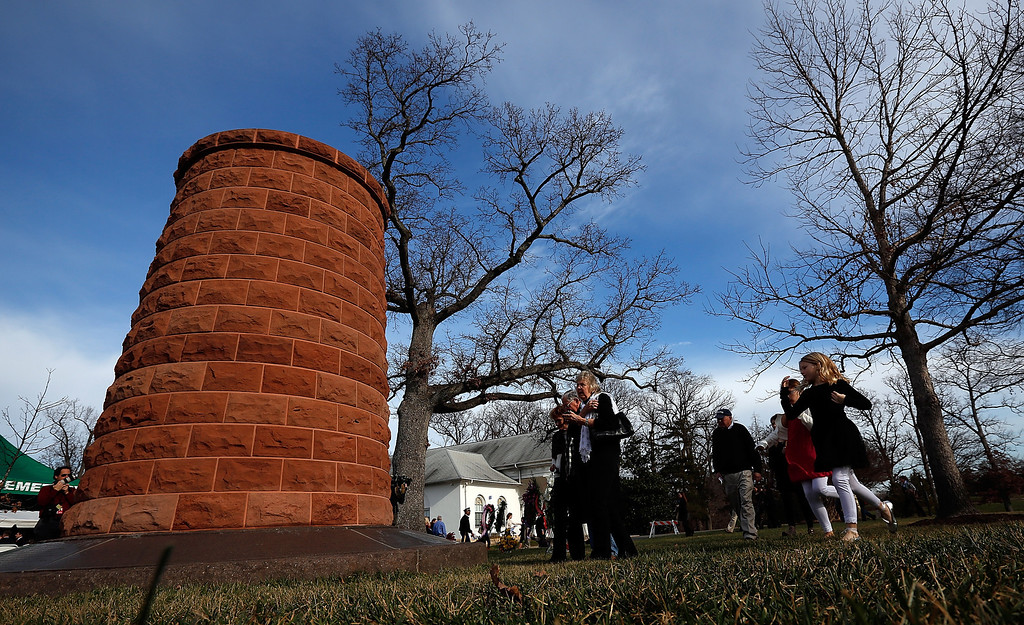. Family members surround a cairn dedicated to those for those who died on Pan Am Flight 103 during a remembrance ceremony at Arlington National Cemetery December 21, 2013 in Arlington, Virginia.  (Photo by Win McNamee/Getty Images)