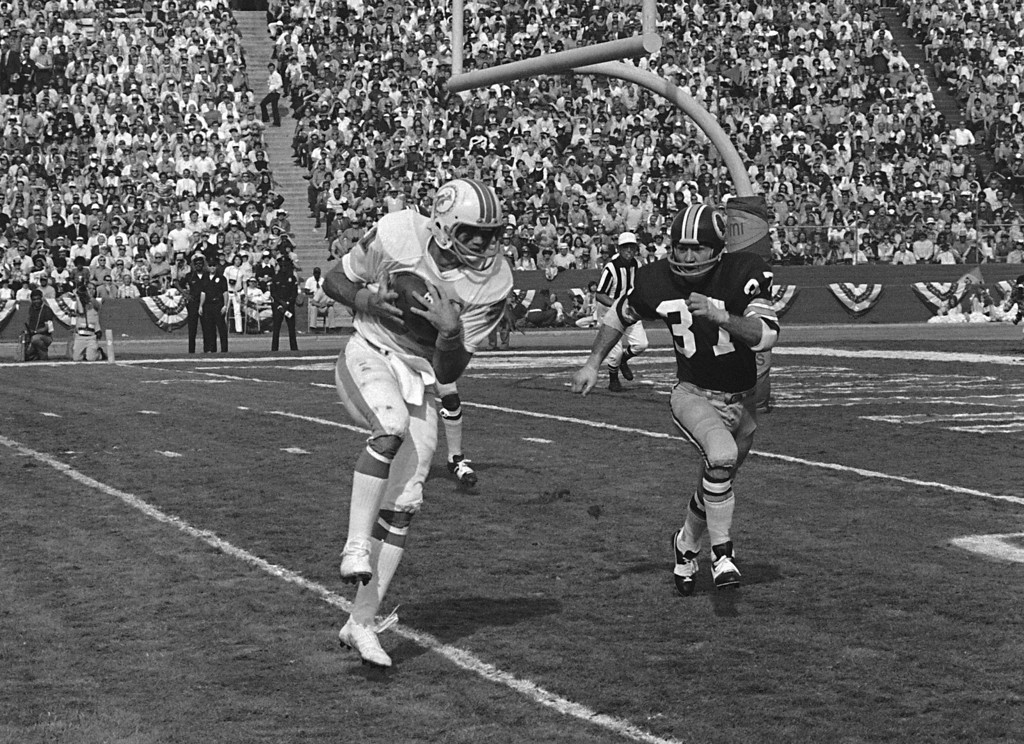 . Miami Dolphins\' Howard Twilley takes in a Bob Griese pass and heads for the end zone for a touchdown in the first quarter of the Super Bowl game in Los Angeles, Jan. 14, 1973.  Washington Redskins\' Pat Fischer (37) chases Twilley.  (AP Photo)