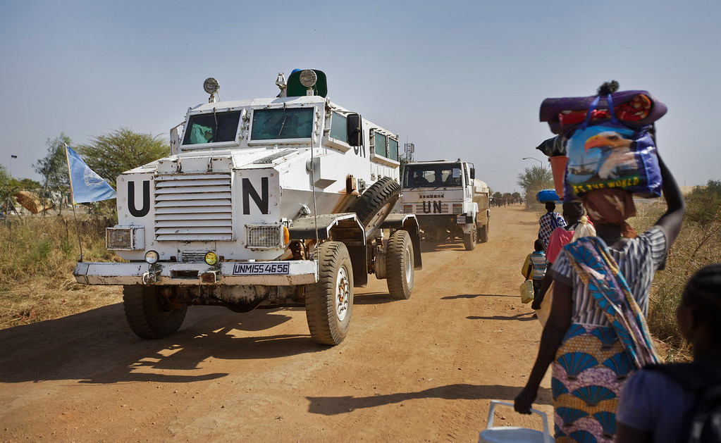 . A United Nations armored vehicle passes displaced people walking towards the U.N. camp where they have sought shelter in Malakal, South Sudan, Monday, Dec. 30, 2013. When violence broke out in Juba on Dec. 15 life remained calm but tense in Malakal, the capital of oil-producing Upper Nile state, but the violence then radiated outward from Juba and full-fledged war broke out in the town on Christmas Day, as army commanders defected and pledged allegiance to the country\'s ousted vice president, in most cases pitting the ethnic group of President Salva Kiir, a Dinka, against ethnic Nuers. (AP Photo/Ben Curtis)