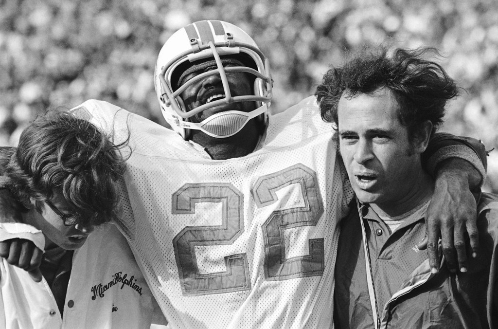 . Dolphins running back Mercury Morris grimaces in pain as he is helped from the Orange Bowl, Saturday, Dec. 16, 1972 in Miami late in the game against Baltimore. Morris was just shy of 1000 yards rushing for the season when he was hurt. The Dolphins won, 16-0, and set a record for having won all 14 season games. (AP Photo)