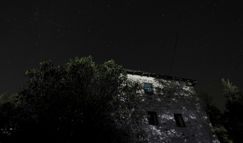 . A meteor shines, top left, while entering the earth\'s atmosphere during the Perseid Meteor Shower observed early Tuesday, Aug. 13, 2013, in this long exposure picture taken from village of Kozle, just southeast of Skopje, Macedonia. (AP Photo/Boris Grdanoski)