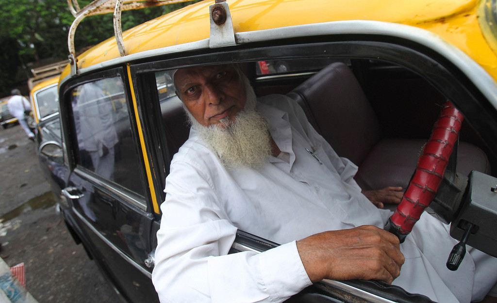 . In this Tuesday, July 30, 2013, an Indian taxi driver poses for photos from inside his vehicle in Mumbai, India. More than 4500 Premier Padmini taxis are expected to be banned from the roads in Mumbai this year, starting in August,  in line with a government order that bans cabs that are more than 20 years old. (AP Photo/Rafiq Maqbool)