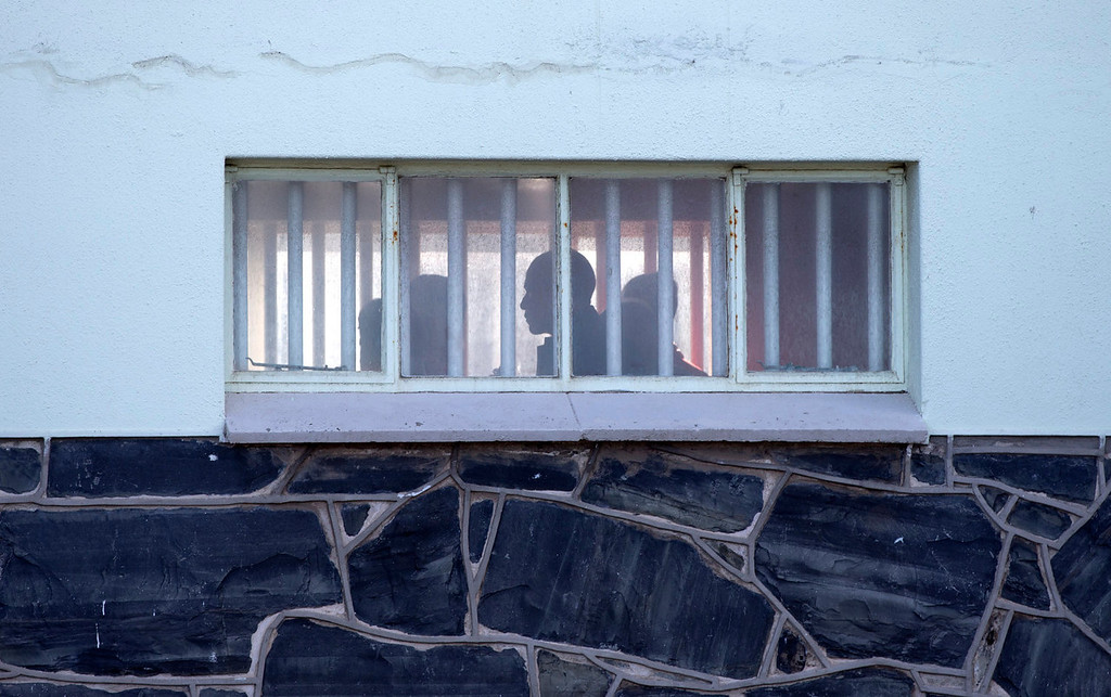 . U.S. President Barack Obama in silhouette, center, walks by a bar covered windows during a tour of the prison on Robben Island, South Africa, Sunday, June 30, 2013. Former South African president Nelson Mandela spent 18 years of his 27-year prison term on the island locked up by the former apartheid government.  (AP Photo/Carolyn Kaster)