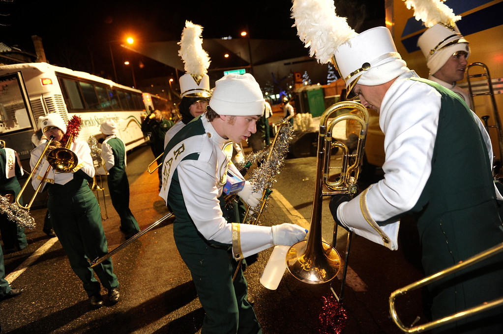 . DENVER, CO. - DECEMBER 06: Colorado State University Marching Band trombonist Matt Evans, center, sprayed pure alcohol on the instruments of band members to reduce freezing as the 9News Parade of Lights kicked off Friday night, December 6, 2013. The weather for the parade was clear but temperatures dipped below zero. Photo By Karl Gehring/The Denver Post