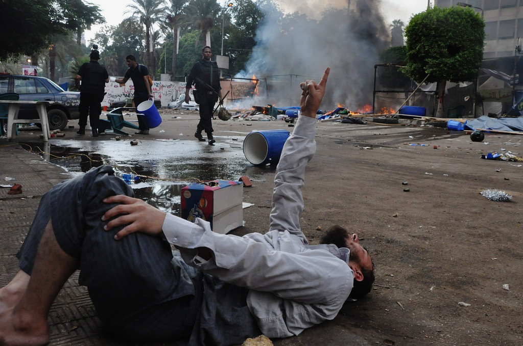 . A man lies on the ground as Egyptian security forces clear a sit-in camp set up by supporters of ousted Islamist President Mohammed Morsi near Cairo University in Cairo\'s Giza district, Egypt, Wednesday, Aug. 14, 2013.  (AP Photo/Hussein Tallal)