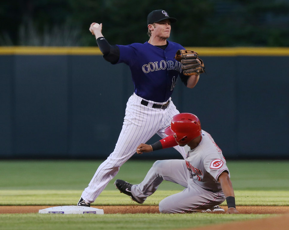 . Colorado Rockies shortstop Josh Rutledge, back, forces out Cincinnati Reds\' Ramon Santiago at second base in the first inning of a baseball game in Denver on Sunday, Aug. 17, 2014. The game is being made up after it was postponed on Saturday by a water main break that left the stadium waterless. (AP Photo/David Zalubowski)