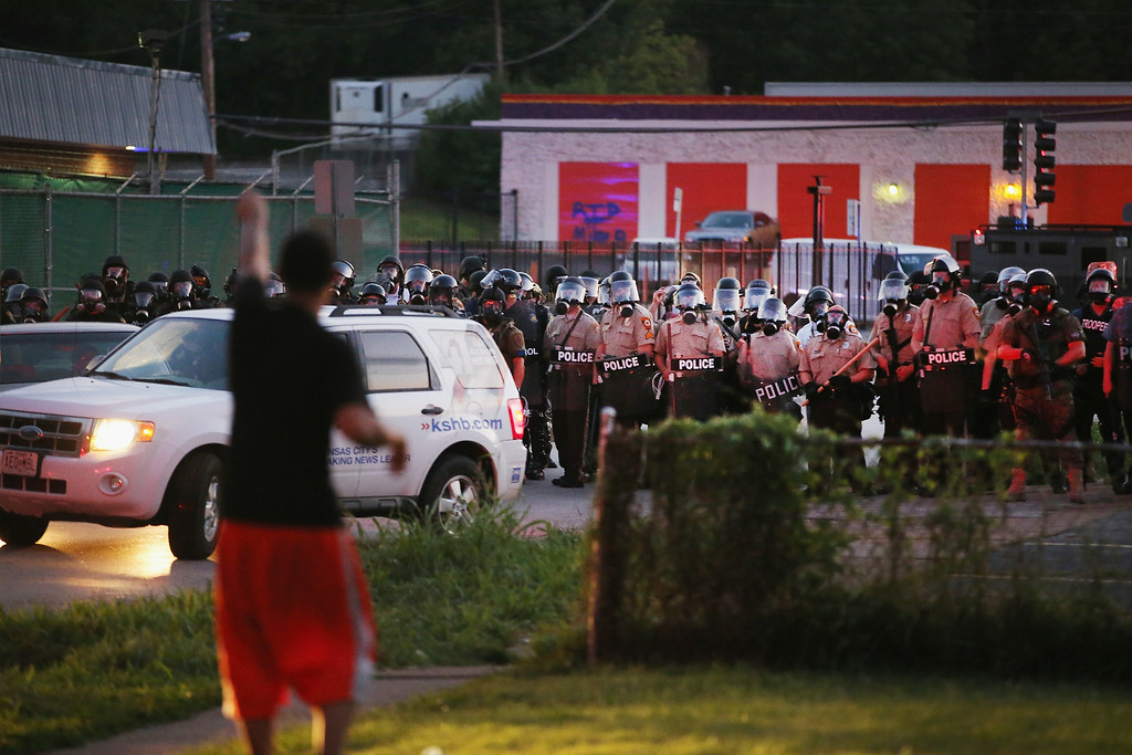 . Police force protestors from the business district into nearby neighborhoods on August 11, 2014 in Ferguson, Missouri. Police responded with tear gas and rubber bullets as residents and their supporters protested the shooting by police of an unarmed black teenager named Michael Brown who was killed Saturday in this suburban St. Louis community. Yesterday 32 arrests were made after protests turned into rioting and looting in Ferguson.  (Photo by Scott Olson/Getty Images)