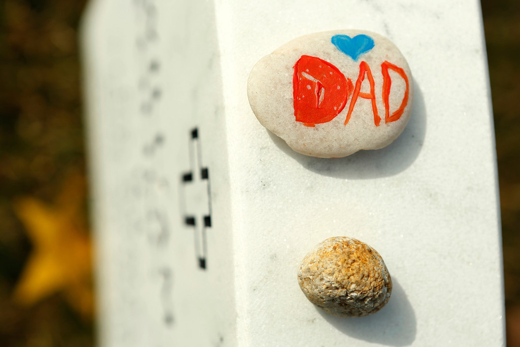 """. \""""Dad\"""" painted on a stone is seen on a headstone in Section 60 at Arlington National Cemetery in Virginia, March 13, 2013. Section 60 contains graves of soldiers from the wars in Iraq and Afghanistan. Picture taken March 13, 2013. REUTERS/Kevin Lamarque"""