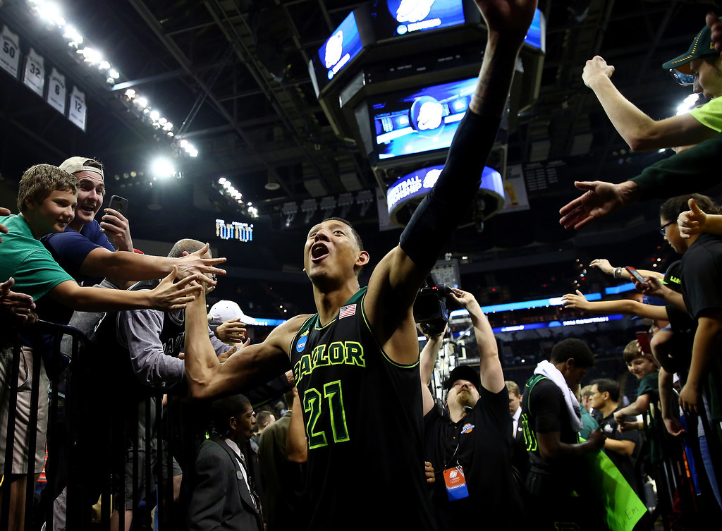 . Isaiah Austin #21 of the Baylor Bears celebrates with fans after defeating the Creighton Bluejays 85-55 in the third round of the 2014 NCAA Men\'s Basketball Tournament at the AT&T Center on March 23, 2014 in San Antonio, Texas.  (Photo by Tom Pennington/Getty Images)