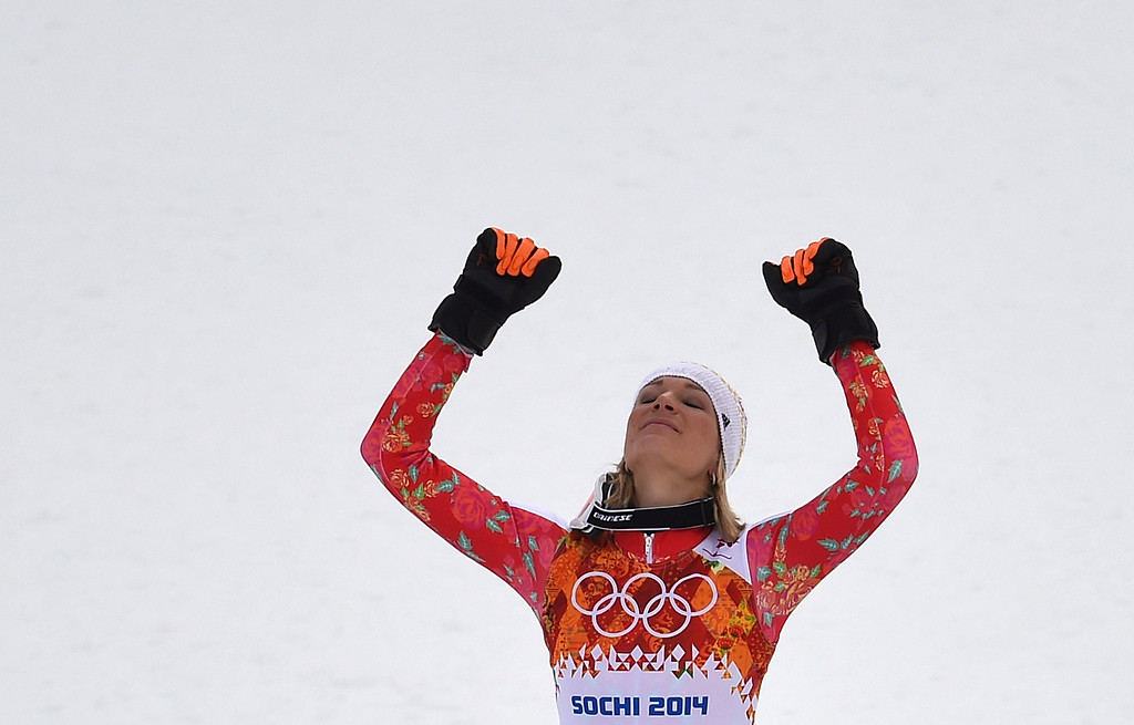 . Gold medallist Germany\'s Maria Hoefl-Riesch raises her arms on the podium after the Women\'s Alpine Skiing Super Combined Flower Ceremony at the Rosa Khutor Alpine Center during the Sochi Winter Olympics on February 10, 2014.    AFP PHOTO / FABRICE COFFRINI/AFP/Getty Images