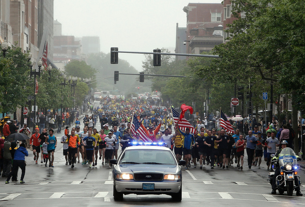 . Runners who were unable to finish the Boston Marathon on April 15 because of the bombings head toward the finish line on Boylston Street after the city allowed them to finish the last mile of the race in Boston, Saturday, May 25, 2013. (AP Photo/Winslow Townson)