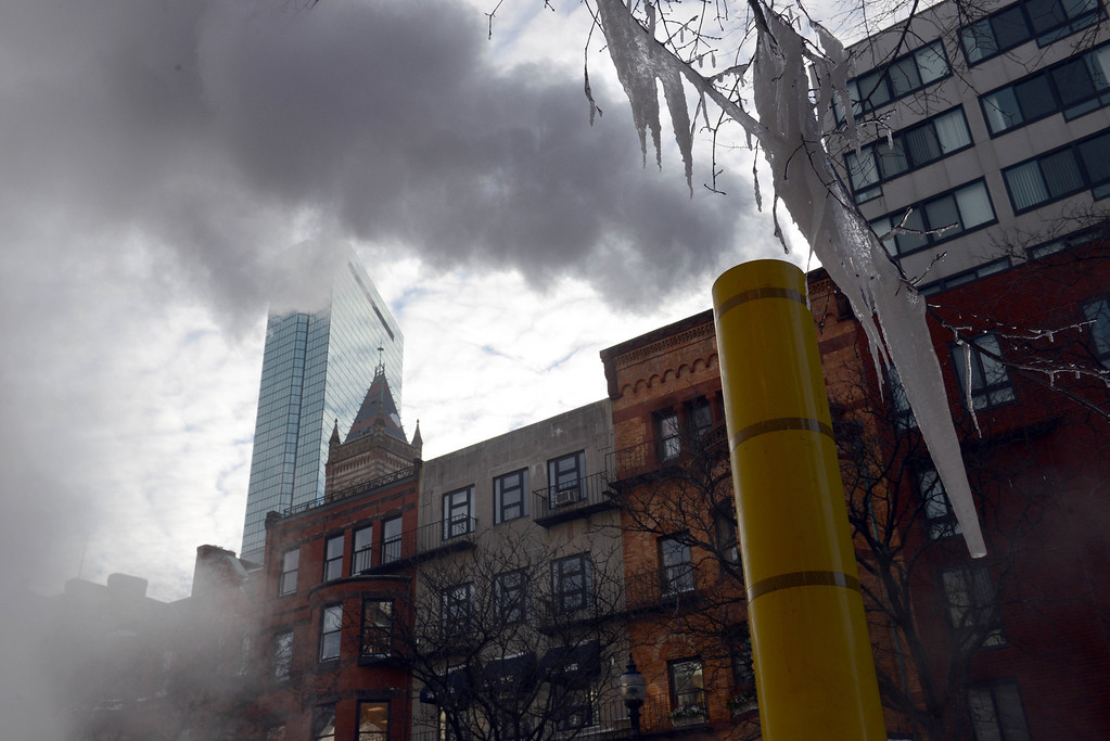 . The John Hancock Tower is seen through the smoke of a construction site from Newbury Street a day after a winter storm January 4, 2014 in Boston, Massachusetts. The storm began mid-day Thursday with heavy snows overnight into Friday bringing with it temperatures in the low single digits and a minus degree wind chill factor.  (Photo by Darren McCollester/Getty Images)