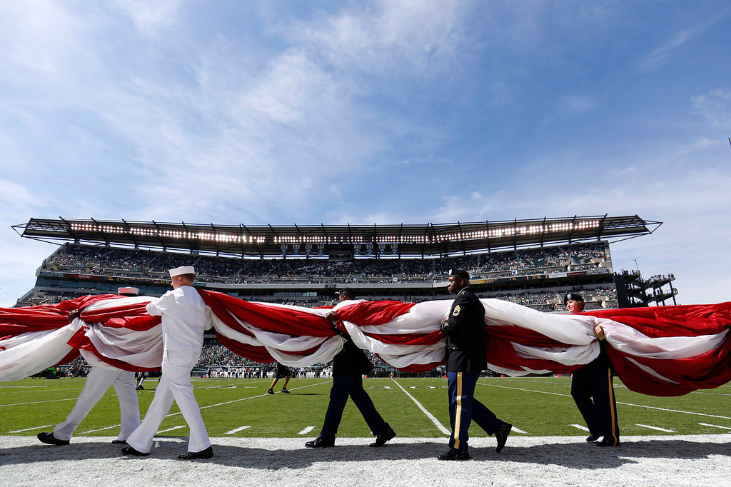 . Military personnel carry an American flag on to the field before an NFL football game between the Philadelphia Eagles and the San Diego Chargers, Sunday, Sept. 15, 2013, in Philadelphia. (AP Photo/Matt Rourke)