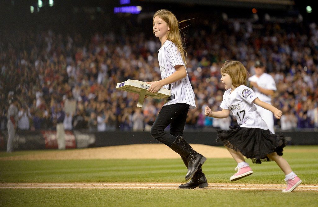 . Tierney Faith Helton (L) and Gentry Grace Helton (R) run off the field with the base in the 9th inning of their game against the Boston Red Sox September 25, 2013 at Coors Field. The girls ran off the field with it as Helton watched. Helton will retire at the end of the season afer 17 years with the club. (Photo By John Leyba/The Denver Post)