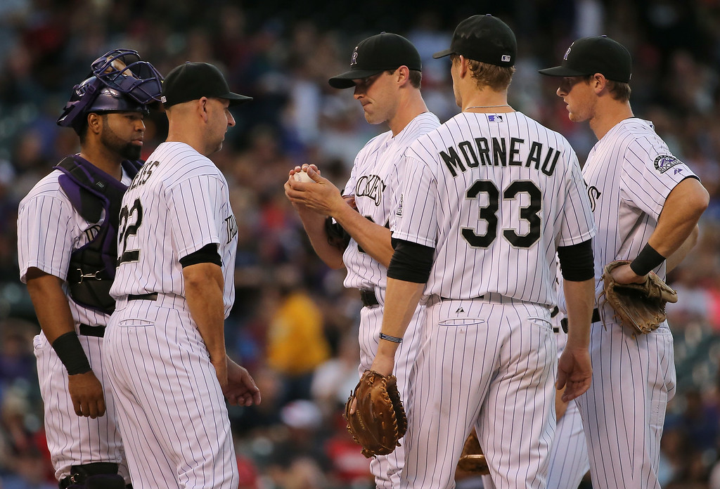 . DENVER, CO - AUGUST 15:  Manager Walt Weiss #22 of the Colorado Rockies visits the mound to talk to starting pitcher Matt Belisle #34 of the Colorado Rockies as he works against the Cincinnati Reds in the third inning at Coors Field on August 15, 2014 in Denver, Colorado.  (Photo by Doug Pensinger/Getty Images)