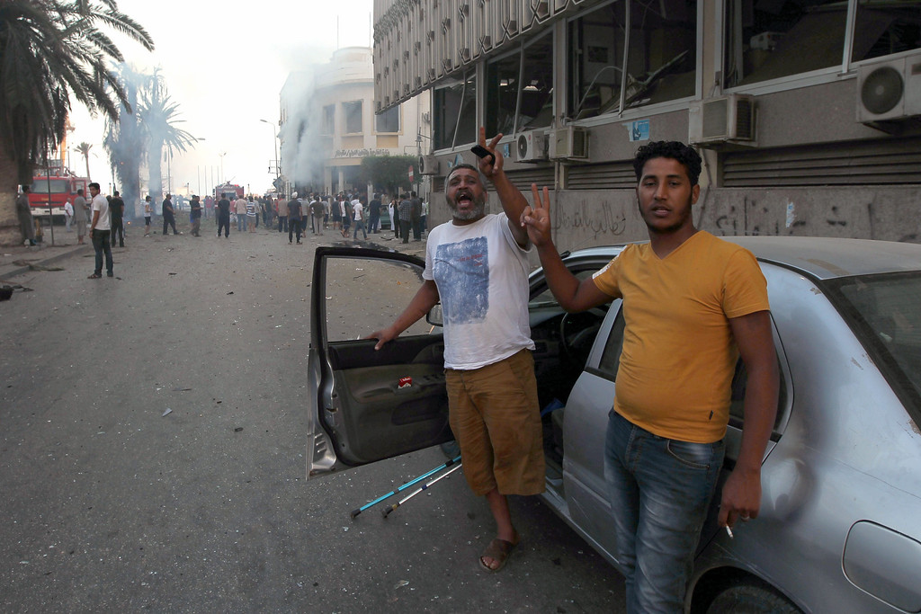 . Libyan men flash the sign of victory in front of a foreign ministry building (background) that was damaged by a powerful blast on September 11, 2013 in the eastern Libyan city of Benghazi. The explosion comes on the first anniversary of an attack by militants on the United States consulate in Benghazi, which killed four Americans, including the ambassador. ABDULLAH DOMA/AFP/Getty Images