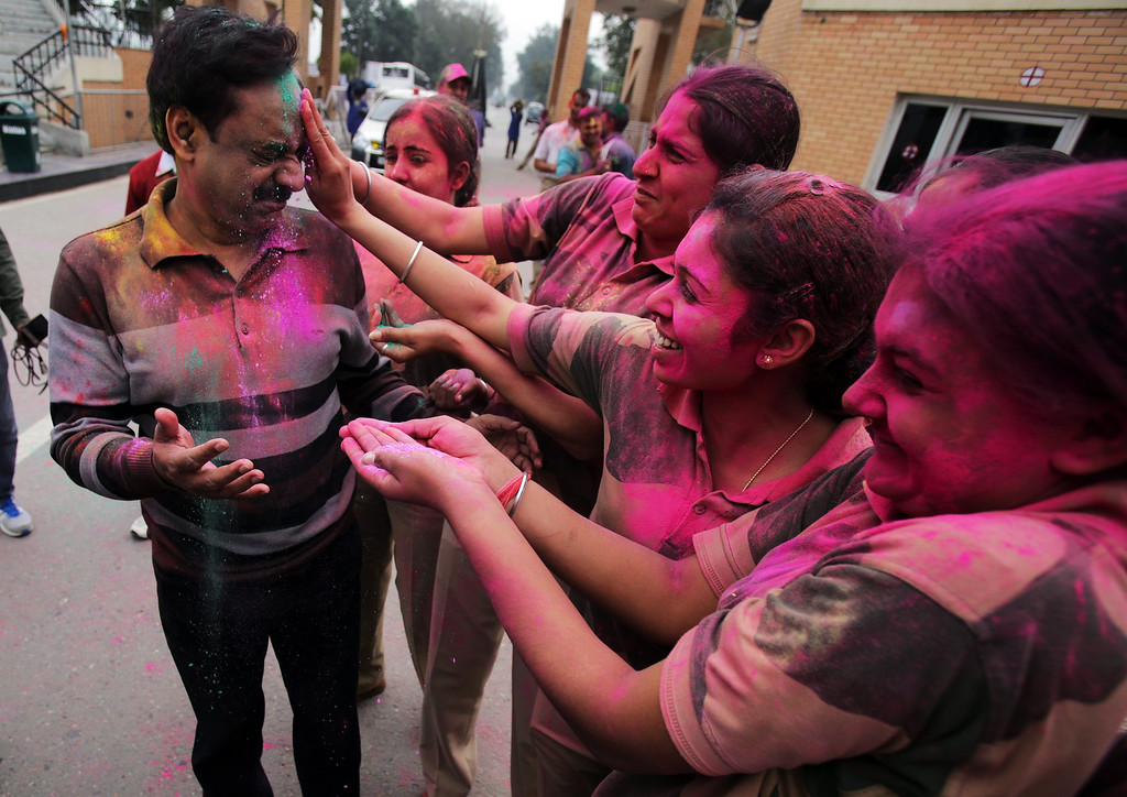 . Indian Border Security Force (BSF) female soldiers smear powdered color on BSF Deputy Inspector General MF Farooqui (L) while celebrating the Holi Festival at the India-Pakistan Joint Check Post (JCP) at the Attari border, some 30 kms from Amritsar, India, 17 March 2014. Holi is celebrated at the end of the winter season on the last full moon day of the lunar month Phalguna (February or March) which usually falls in the later part of February or March and main day is celebrated by people throwing colored powder and colored water at each other.  EPA/RAMINDER PAL SINGH