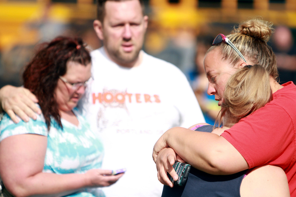 . People comfort each other as they await word about the safety of students after a shooting at Reynolds High School Tuesday, June 10, 2014, in Troutdale, Ore.  (AP Photo/The Oregonian, Faith Cathcart)