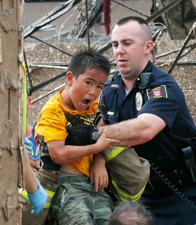 . A boy is pulled from beneath a collapsed wall at the Plaza Towers Elementary School following a tornado in Moore, Okla., Monday, May 20, 2013. A tornado as much as a mile (1.6 kilometer) wide with winds up to 200 mph (320 kph) roared through the Oklahoma City suburbs Monday, flattening entire neighborhoods, setting buildings on fire and landing a direct blow on the elementary school. (AP Photo Sue Ogrocki)