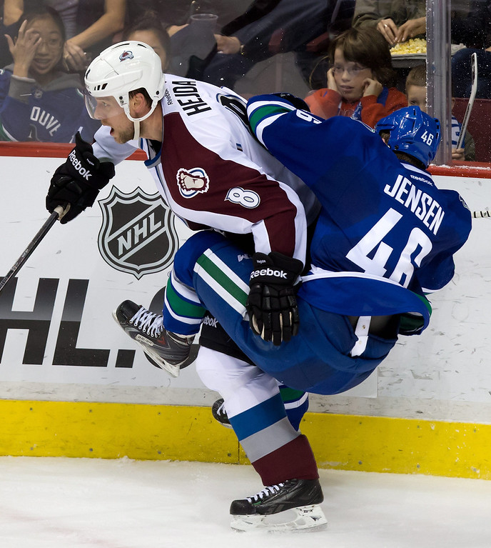 . Colorado Avalanche\'s Jan Hejda, left, of the Czech Republic, and Vancouver Canucks\' Nicklas Jensen, of Denmark, collide during the second period of an NHL hockey game Thursday, April 10, 2014, in Vancouver, British Columbia. (AP Photo/The Canadian Press, Darryl Dyck)