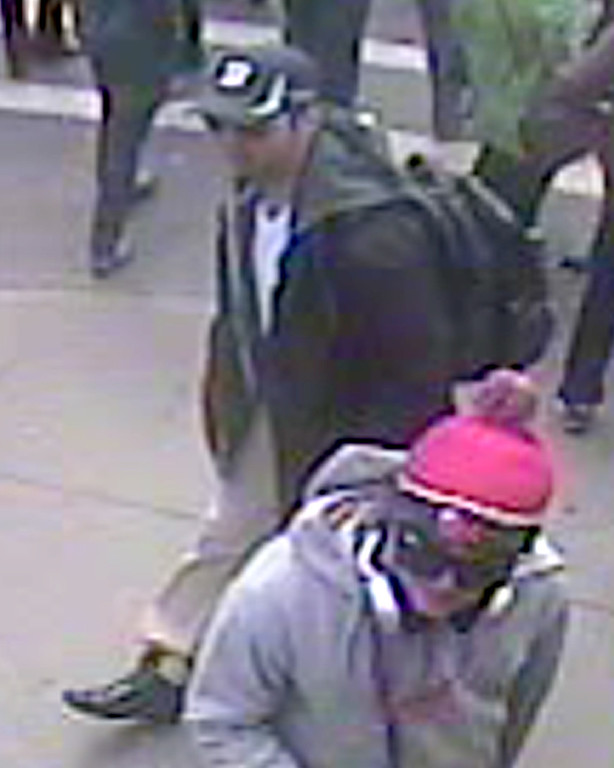 """. This image taken from a video released by the FBI on April 18, 2013 shows a man with a backpack walking along the route of the Boston Marathon on April 15. The man and one other are being sought by the FBI in connection with the marathon bombing that killed three. The US Federal Bureau of Investigation (FBI) released the photos and videos of two men sought as suspects in the Boston bombings, urging the public to help identify them. \""""No bit of information... is too small for us to see,\"""" Richard DesLauriers, the agent in charge of the FBI\'s Boston office, told a press conference.  /AFP/Getty Images"""