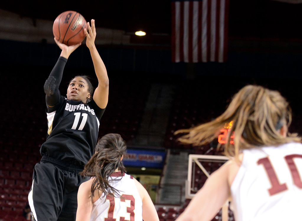 . University of Colorado\'s Brittany Wilson takes a shot over Emiko Smith during a games against the University of Denver on Tuesday, Dec. 11, at the Magnus Arena on the DU campus in Denver.   (Jeremy Papasso/Daily Camera)