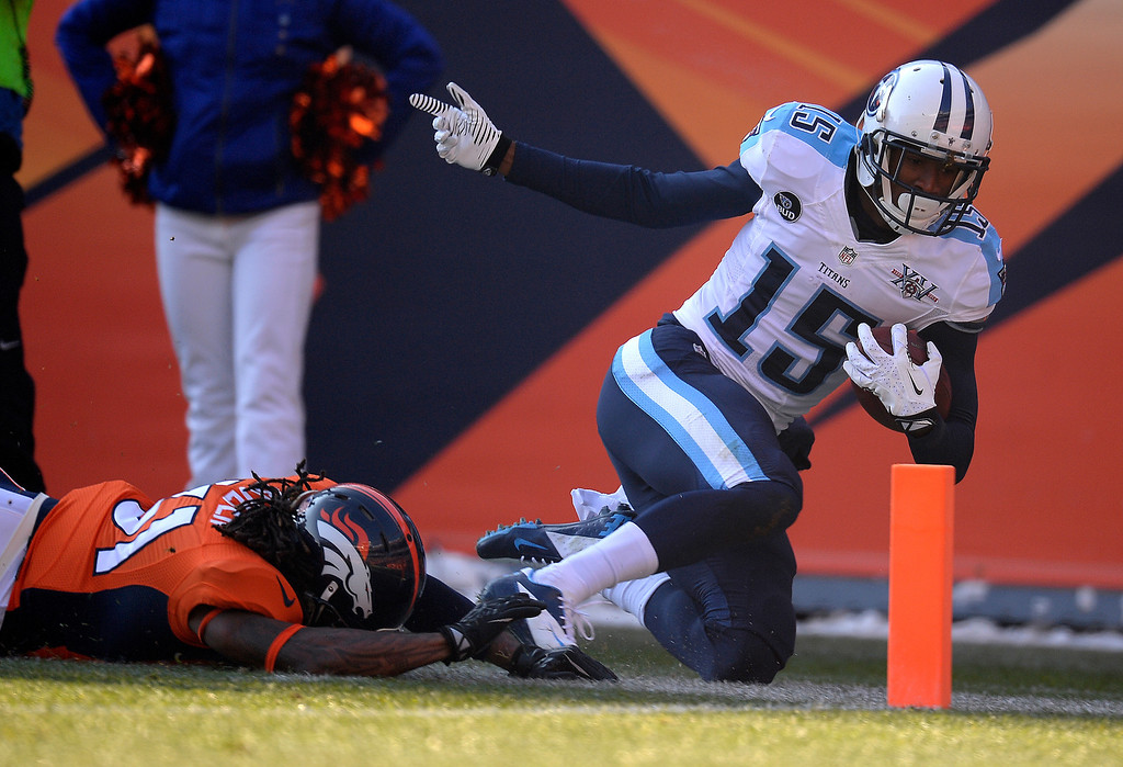 . Tennessee Titans wide receiver Justin Hunter (15) makes a catch for a gain of 57 yards and is pushed out of bounds by Denver Broncos cornerback Omar Bolden (31) at the one yard line.  (Photo by John Leyba/The Denver Post)