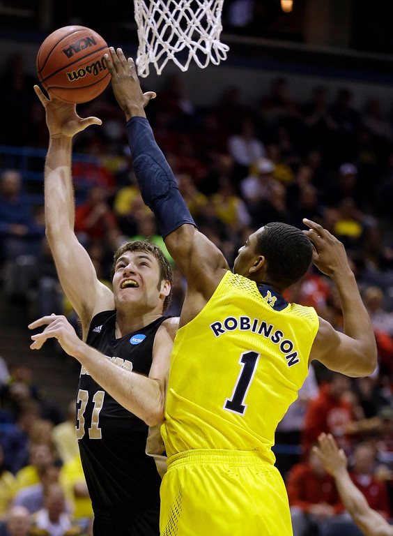 . Wofford forward C.J. Neumann (31) takes a shot over Michigan forward Glenn Robinson III (1) during the first half of a second round NCAA college basketball tournament game Thursday, March 20, 2014, in Milwaukee. (AP Photo/Jeffrey Phelps)