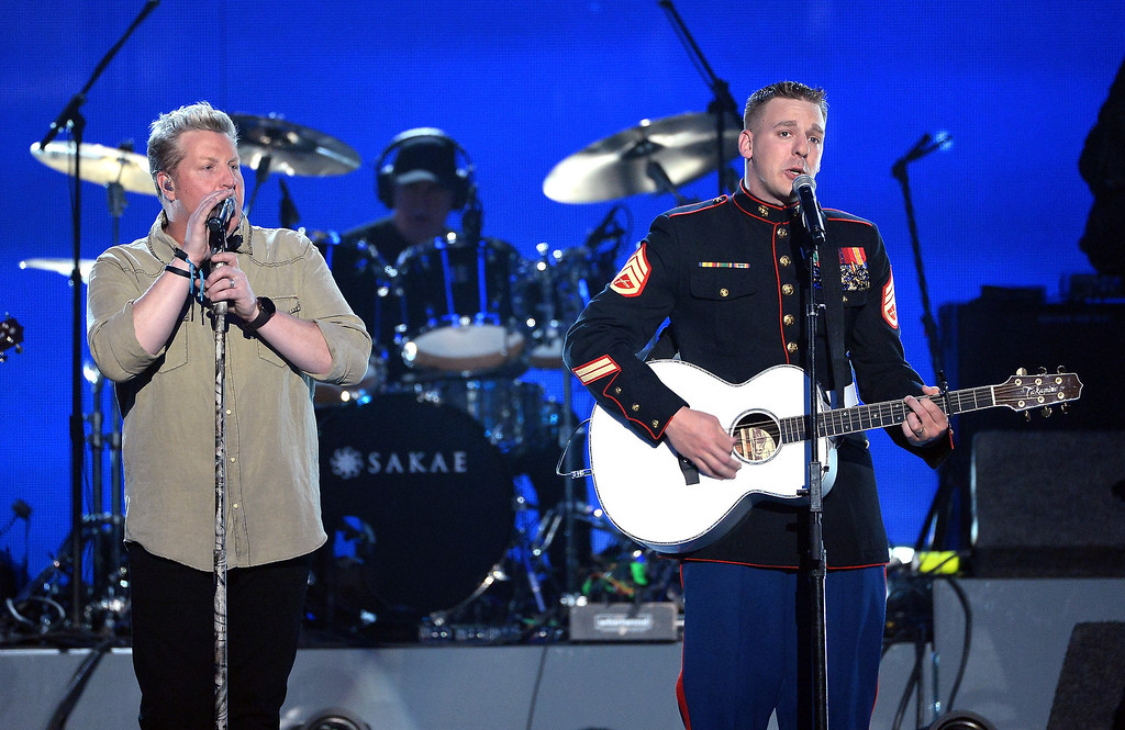 . Singer Gary LeVox of Rascal Flatts (L) and Marine Staff Sgt. Brandon Valentine perform onstage during ACM Presents: An All-Star Salute To The Troops at the MGM Grand Garden Arena on April 7, 2014 in Las Vegas, Nevada.  (Photo by Ethan Miller/Getty Images for ACM)