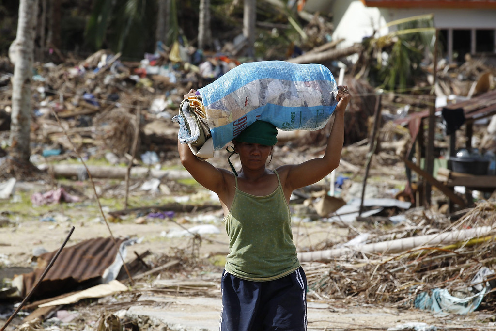 . A Filipino woman carries a sack of relief goods through typhoon debris in the coastal village of Batang in Eastern Samar Province, Philippines, 21 November 2013.  EPA/ROLEX DELA PENA