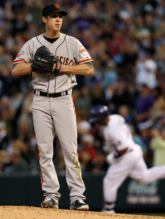 . San Francisco Giants starting pitcher Tim Lincecum, foreground, reacts as Colorado Rockies\' Wilin Rosario, background, rounds the bases after hitting a two-run home run in the fifth inning of a baseball game in Denver, Saturday, May 18, 2013. (AP Photo/David Zalubowski)