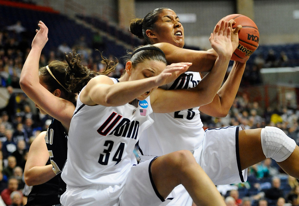 . Connecticut\'s Kaleena Mosqueda-Lewis, right, pulls down a rebound against Idaho\'s Connie Ballestero, left, as Connecticut\'s Kelly Faris (34) defends in the second half of a first-round game in the women\'s NCAA college basketball tournament in Storrs, Conn., Saturday, March 23, 2013. Connecticut won 105-37. (AP Photo/Jessica Hill)