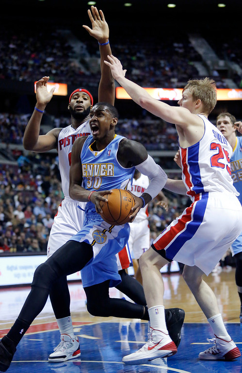 . Denver Nuggets forward Quincy Miller (30) drives to the basket between Detroit Pistons center Andre Drummond, left, and guard Kyle Singler (25) during the first half of an NBA basketball game on Saturday, Feb. 8, 2014, in Auburn Hills, Mich. (AP Photo/Duane Burleson)