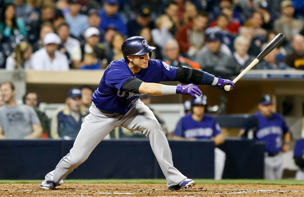 . Colorado Rockies\' Troy Tulowitzki reaches out to slap a single to left field against the San Diego Padres in the fifth inning of a baseball game Monday, April 14, 2014, in San Diego. (AP Photo/Lenny Ignelzi)